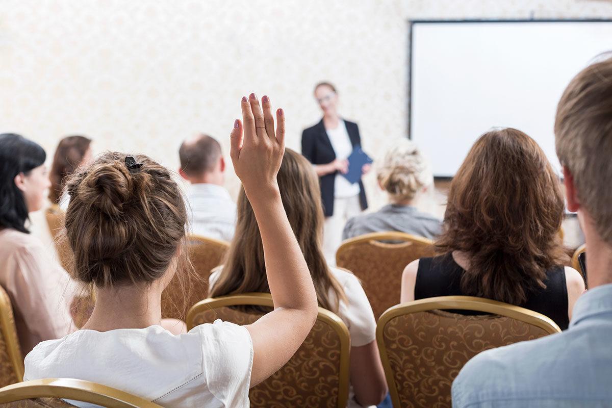 Illustrasjon av person som rekker hånden i været for å stille spørsmål